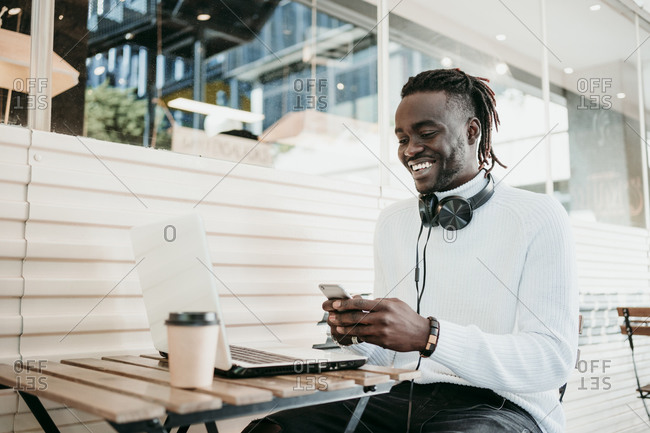 Smiling creative businessman with laptop using mobile phone in cafe