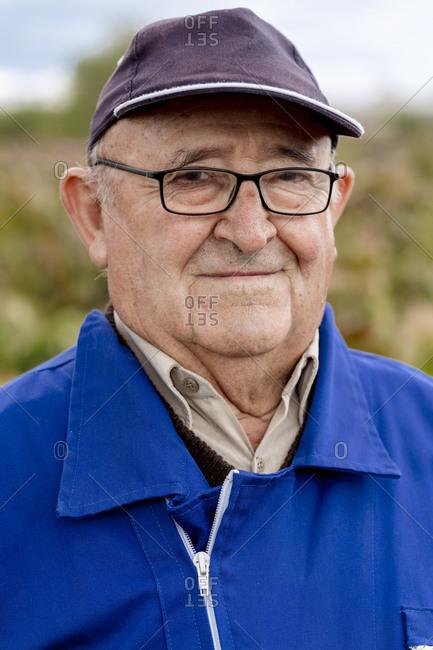 Senior man with cap and eyeglasses against grape farm