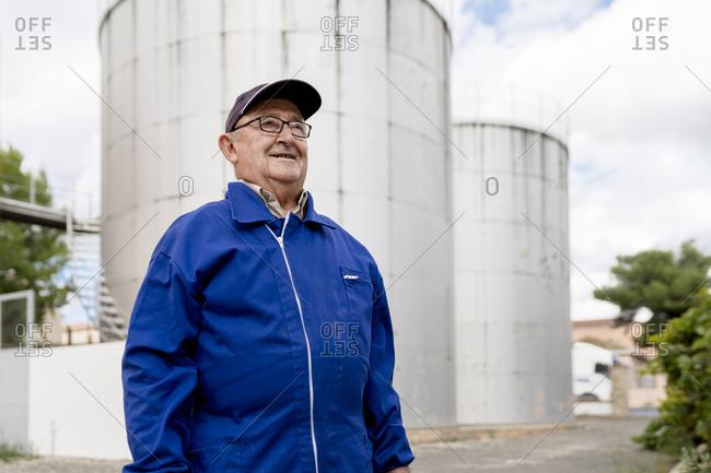 Senior male winemaker against stainless steel vat at winery