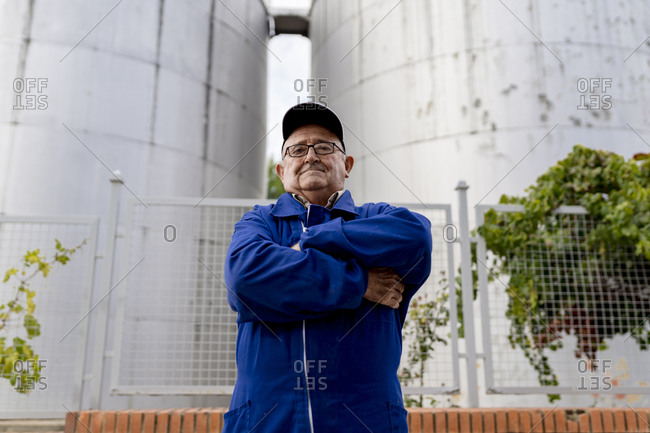 Elderly male winemaker with arms crossed against stainless steel vat at winery industry