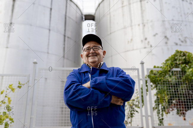 Senior male winemaker with arms crossed against stainless steel vat at winery