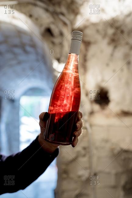 Senior male winemaker holding bottle of rose wine