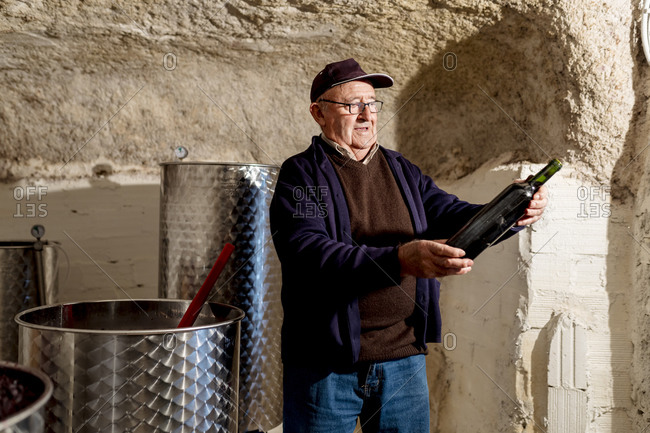 Senior male winemaker holding bottle of red wine at winery