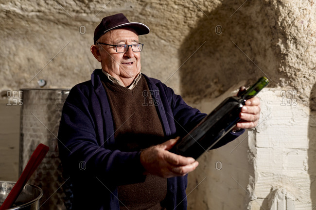 Smiling male winemaker holding bottle of red wine at winery