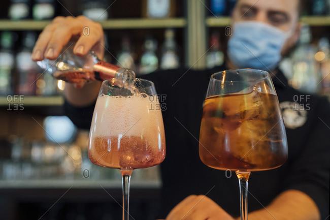 Waiter in bar preparing drinks in restaurant