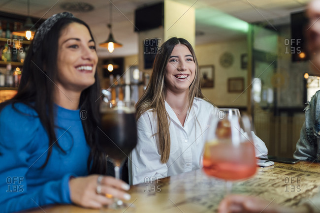 Smiling female friends enjoying drinks in bar