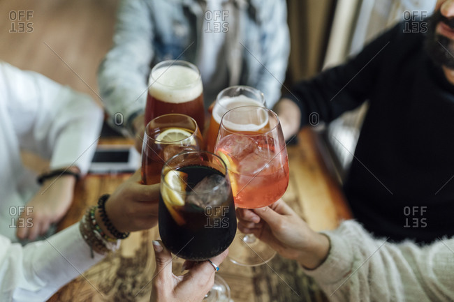 Friends hands toasting glasses at bar