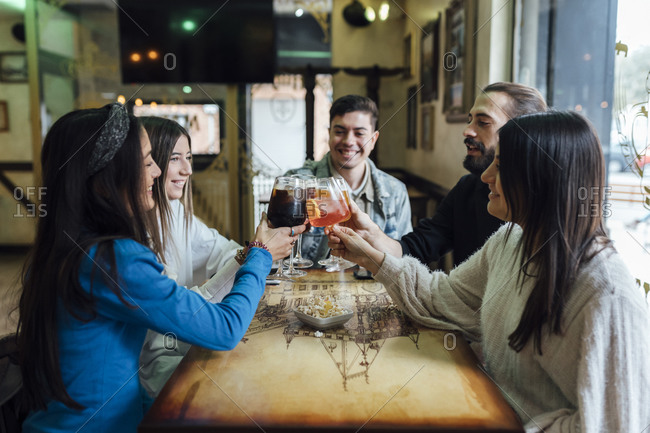 Smiling friends toasting drinks over table in bar