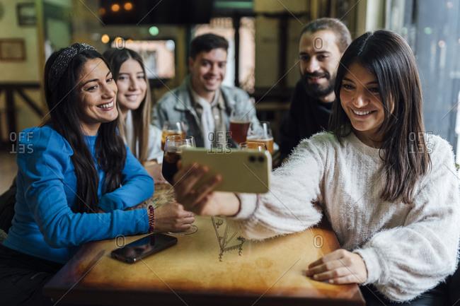 Smiling friends taking selfie on smart phone in bar