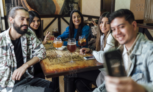 Happy friends taking selfie through smart phone in bar