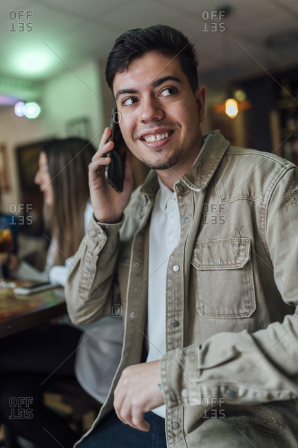Smiling man talking on mobile phone while looking away in bar
