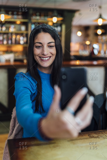 Attractive woman taking selfie on smart phone in bar