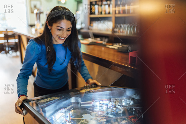 Attractive woman playing pinball in bar