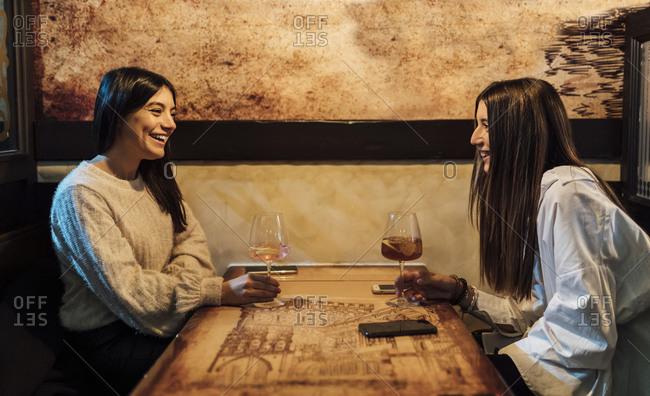Smiling female friends having drinks in bar