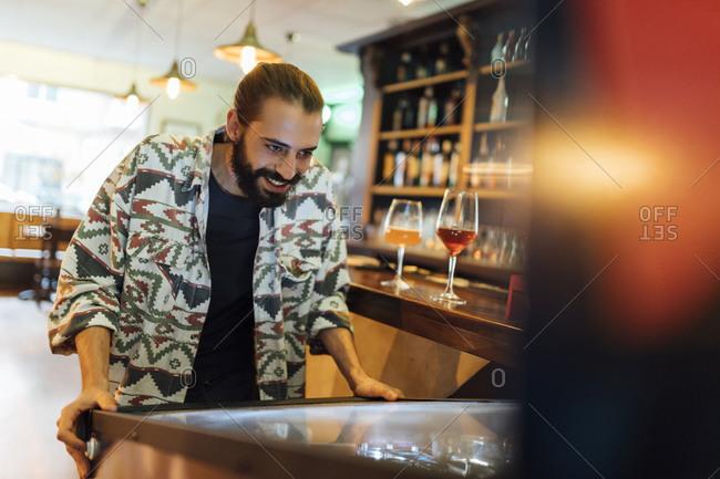 Bearded man playing pinball in bar