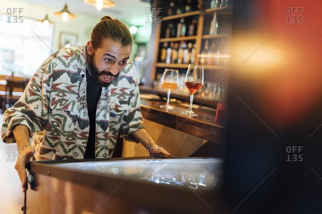 Cheerful bearded man playing pinball in bar