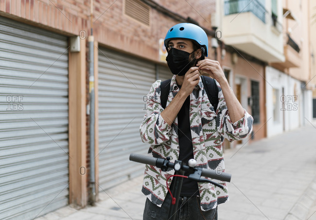 Young man with protective face mask on electric push scooter in city