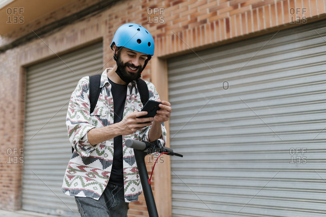 Young man with electric push scooter using smart phone while standing by shutter