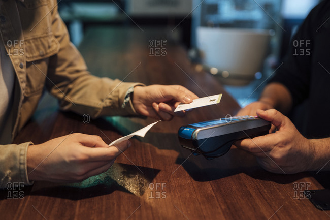 Man's hands paying with credit card in restaurant