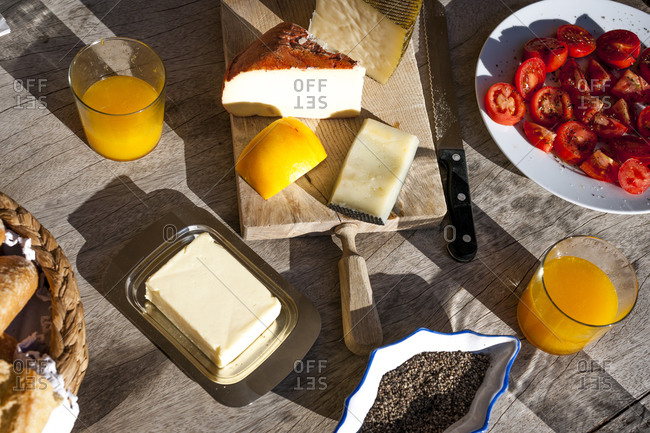 Plate with sliced tomatoes- two glasses of orange juice- butter- pepper and cutting board with different cheese