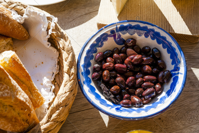Bowl of dates lying next to basket with bread