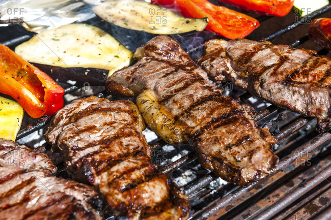 Meat and vegetables being grilled on barbecue grill