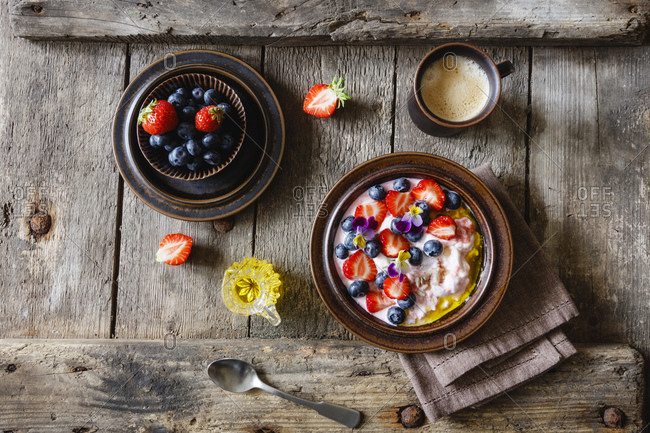 Cup of coffee and plate of quark with strawberries- blueberries and edible flowers
