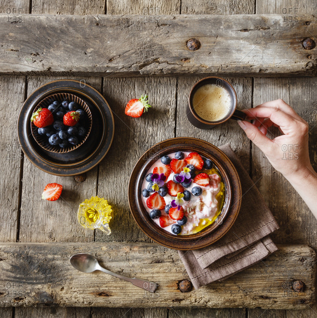 Female hand reaching for cup of coffee standing beside plate of quark with fruits and edible flowers