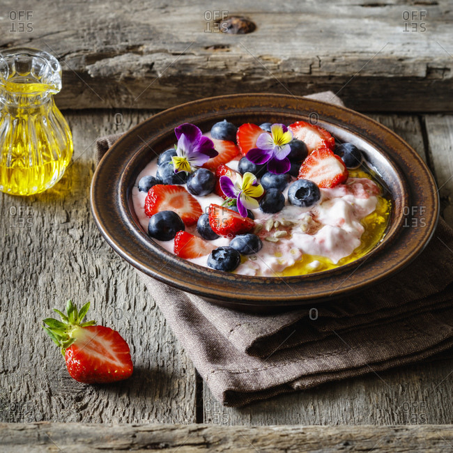 Plate of quark with strawberries- blueberries and edible flowers