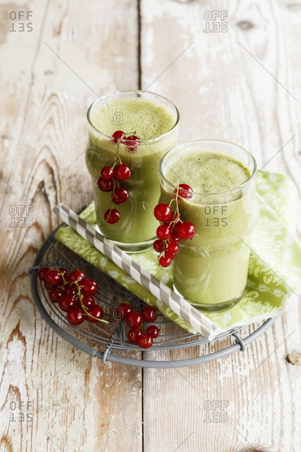 Fresh red currant berries and two glasses of green smoothie