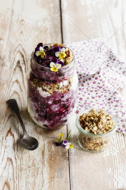 Jar of yogurt with blueberries- muesli and edible flowers