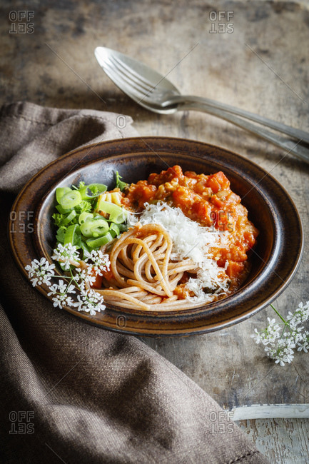 Plate of vegetarian spaghetti Bolognese with wildflowers- scallion and grunkern spelt