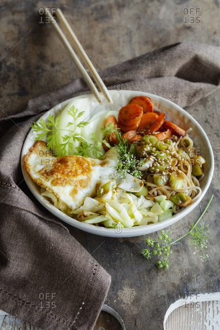 Bowl of soba noodles with cabbage- carrots- kohlrabi- fried egg and herbs