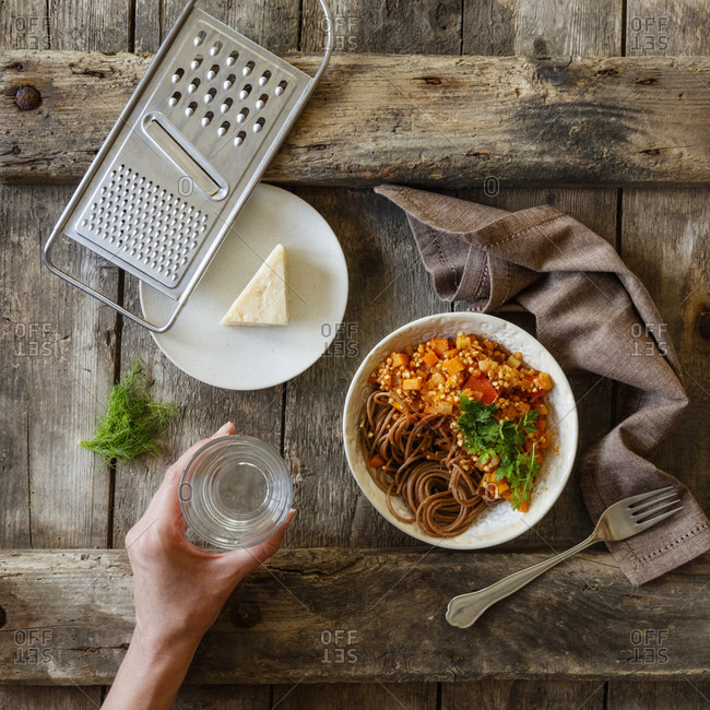 Bowl of vegetarian spaghetti Bolognese and hand of woman holding glass of water