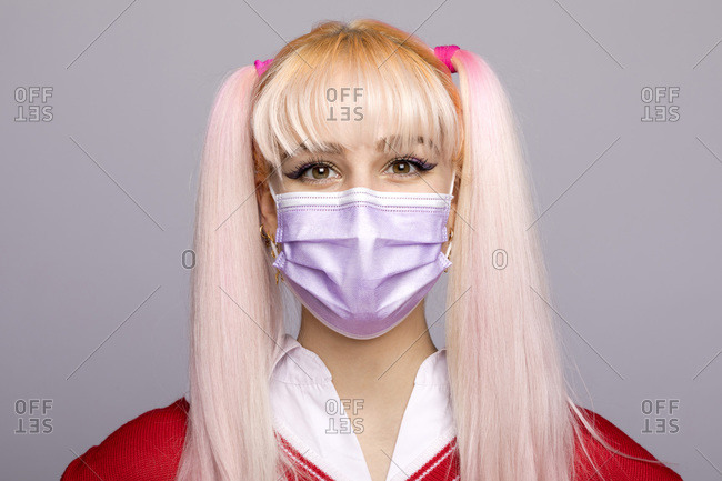 Beautiful young woman with dyed long hair wearing face mask during pandemic