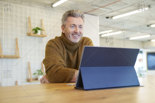 Mature man smiling while using digital tablet sitting at home