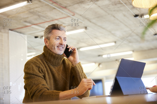 Man talking on mobile phone while using digital tablet sitting at home