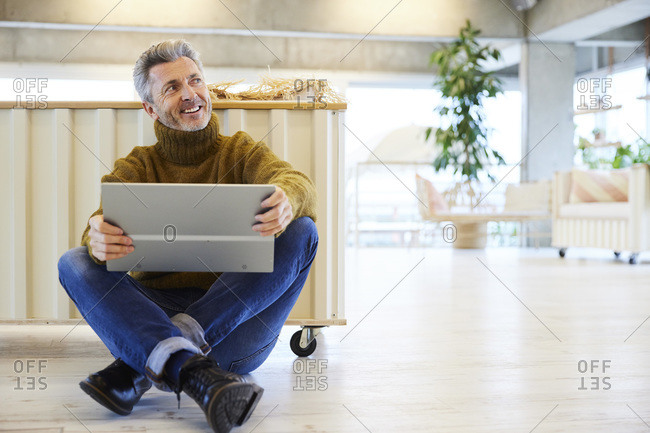 Smiling man with digital tablet looking away while sitting on floor at home