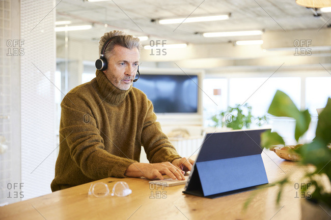 Businessman wearing headset talking while working on digital tablet at office