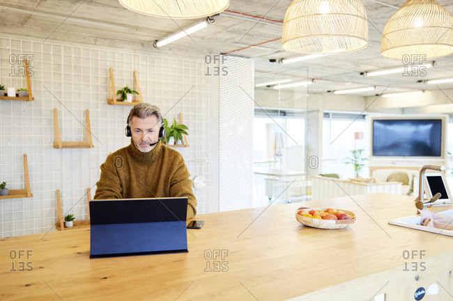 Mature businessman wearing headset using digital tablet while sitting at office