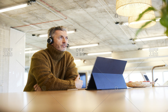 Thoughtful businessman with headset and digital tablet looking away while sitting at office