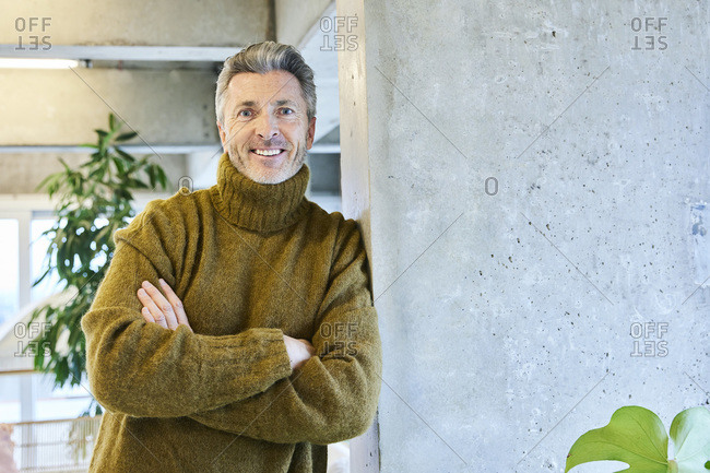 Mature man with arms crossed smiling while leaning on pillar at office
