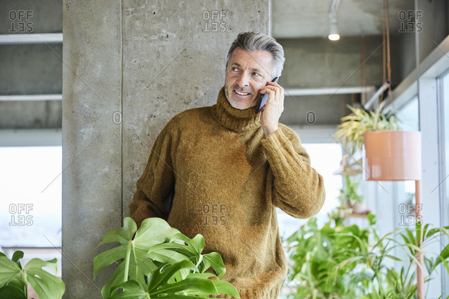 Man talking on mobile phone while leaning on pillar at office