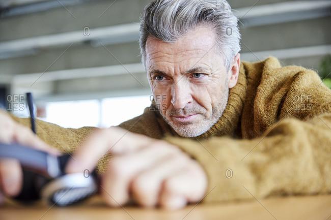Man repairing headset while sitting at office