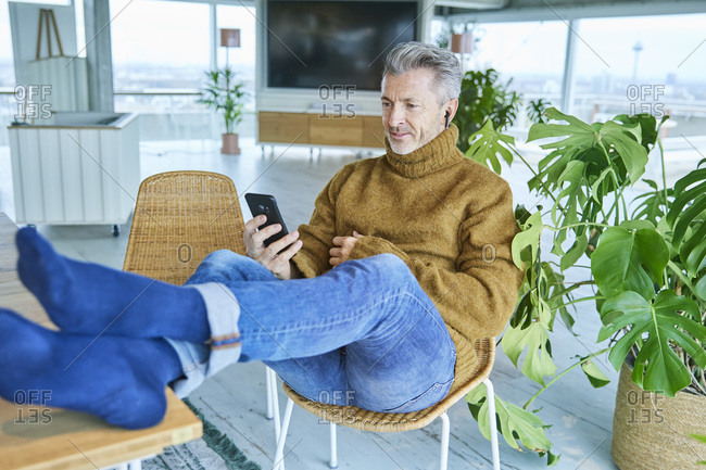 Man wearing in-ear headphones using mobile phone while relaxing on chair at home