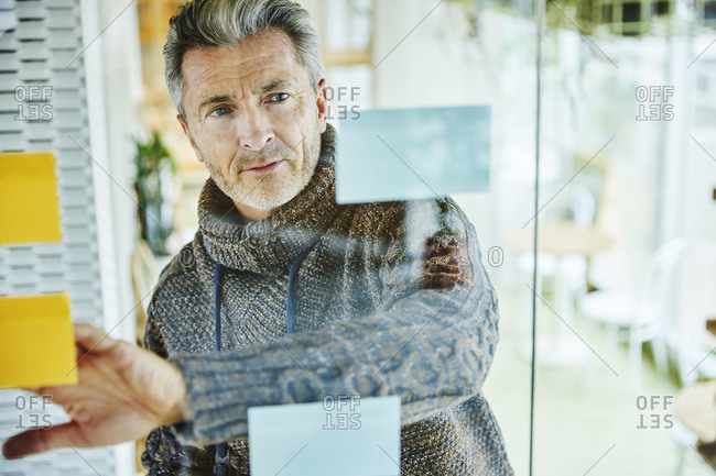 Mature businessman putting adhesive note on glass wall while standing at office