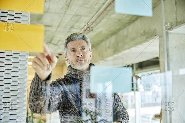 Businessman planning strategy while standing by glass wall at office