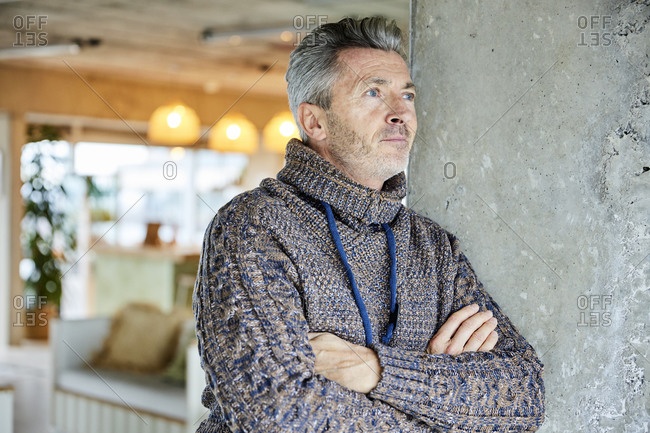 Thoughtful man looking away while leaning on wall at office