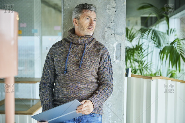 Mature businessman with digital tablet looking away while standing at office