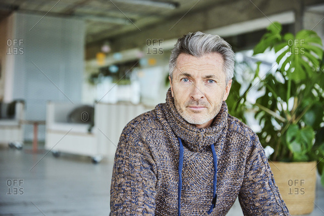 Mature man with blue eyes staring while sitting at office